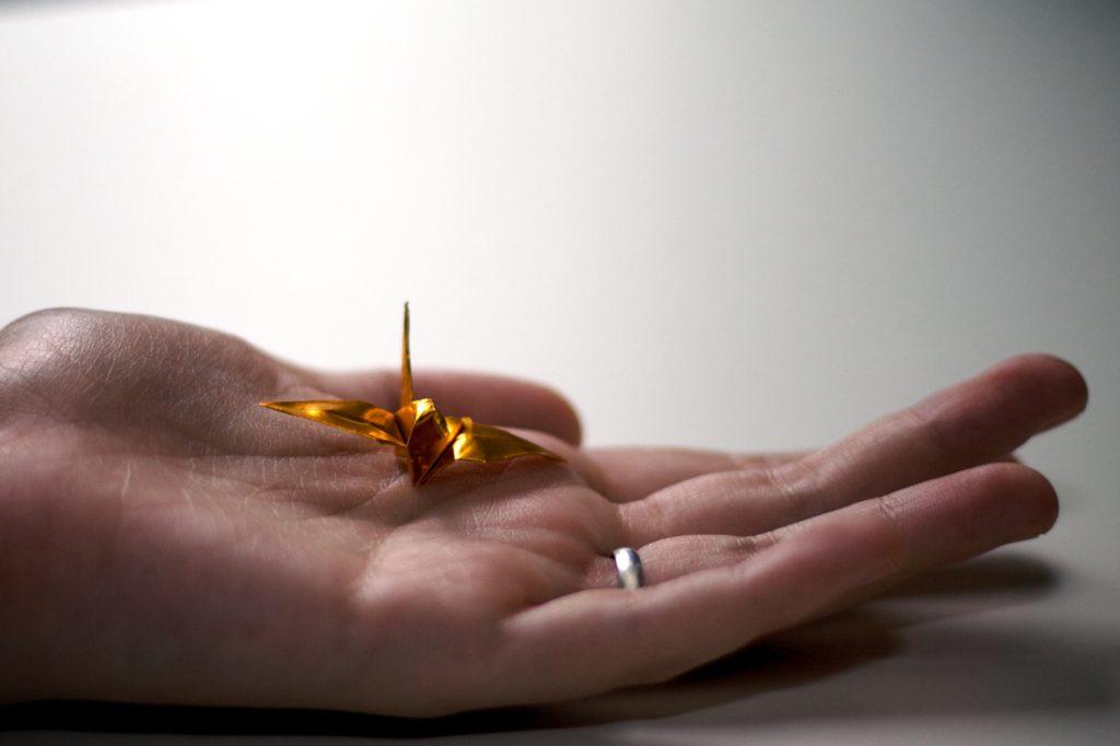 hand holding a golden origami crane