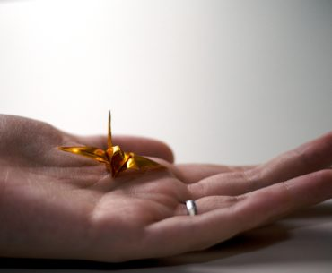 hand holding a golden origami crane